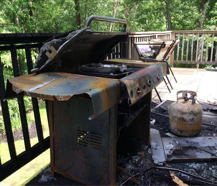 A photo of a melted grill on an outdoor deck. The whole space is charred and black.